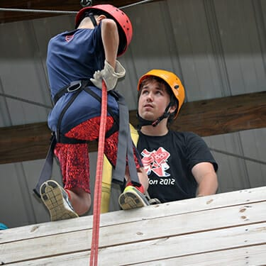 Activity Period Adventure At Camp - Camper going down rappel wall on ropes course - Cub Creek Science and Animal Camp