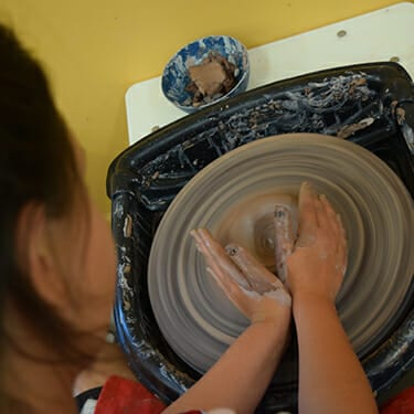 Activity Period Arts And Crafts At Camp - Camper in pottery studio - pottery wheel - Cub Creek Science and Animal Camp