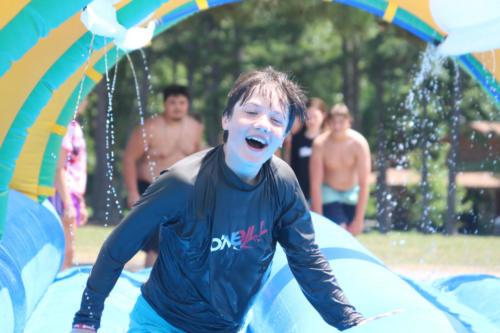 Camper having fun on inflatable - Cub Creek Science Camp
